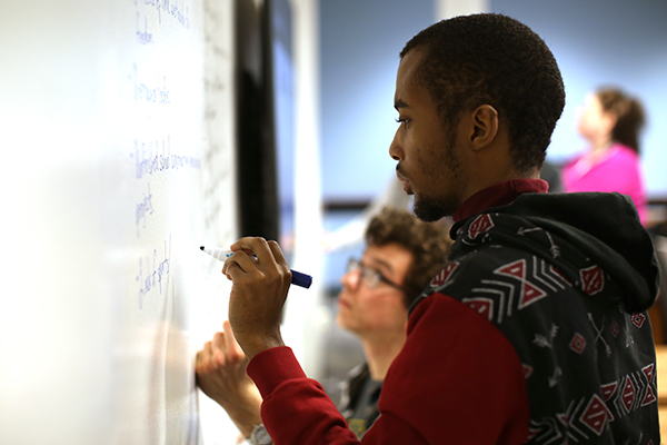 Male student draws on white board