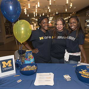 Three students stand together wearing Michigan Library tshirts at a table.