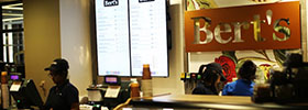 Student worker behind cash register at Bert's cafe