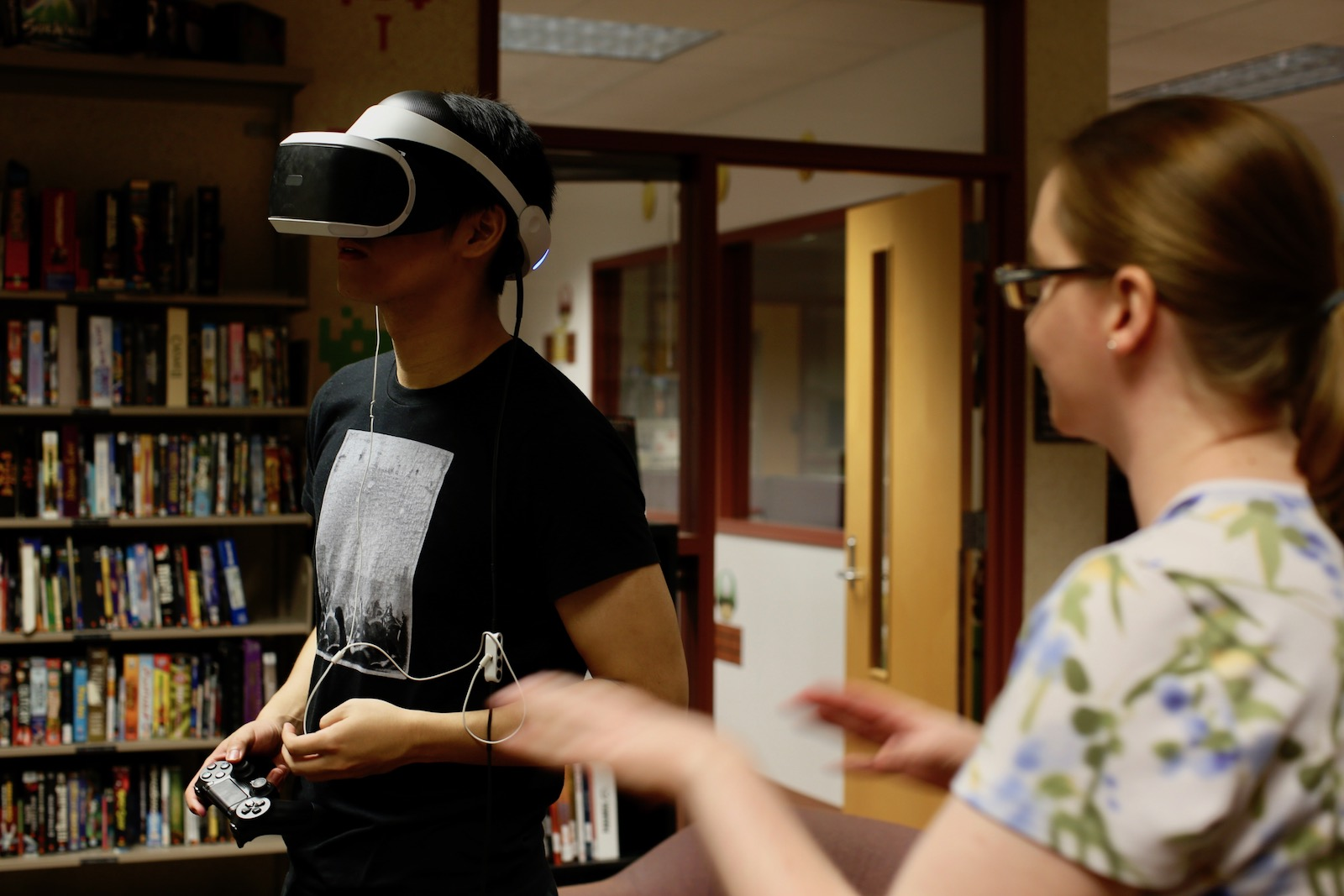 Photo of a man wearing a virtual reality headset with a woman looking on