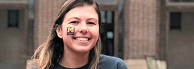 photo of a smiling student with a library tattoo on her cheek