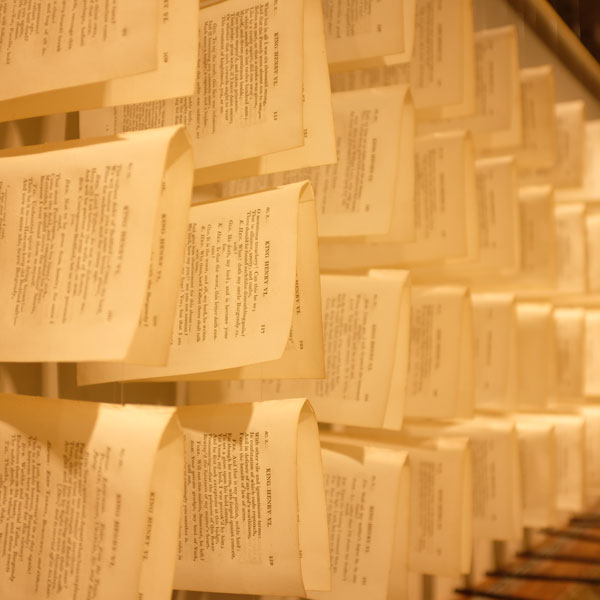 Book pages taken from books and hung with fishing line so they're hovering in a grid as part of an art installation.