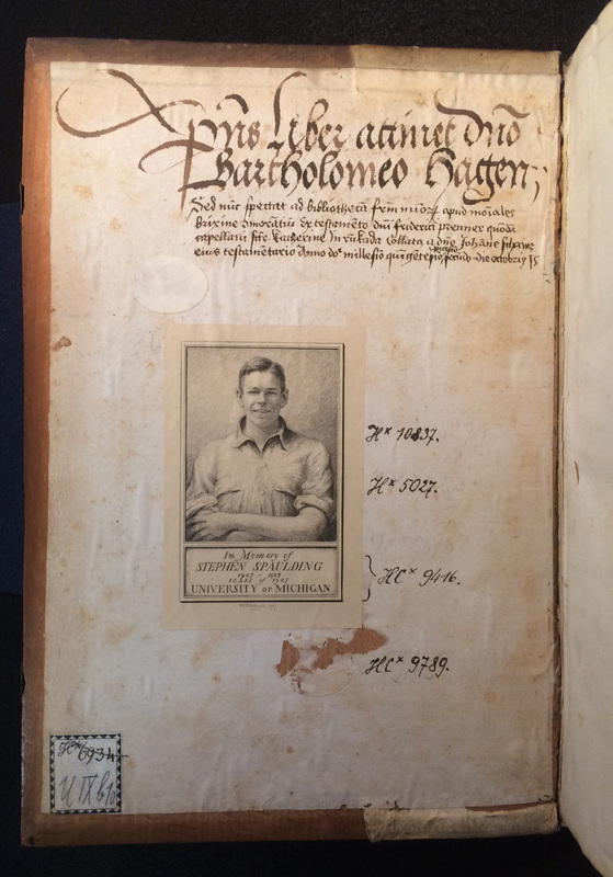 The inside cover of an old book, with handwritten text in Latin and a bookplate In Memory of Stephen Spaulding that includes his image