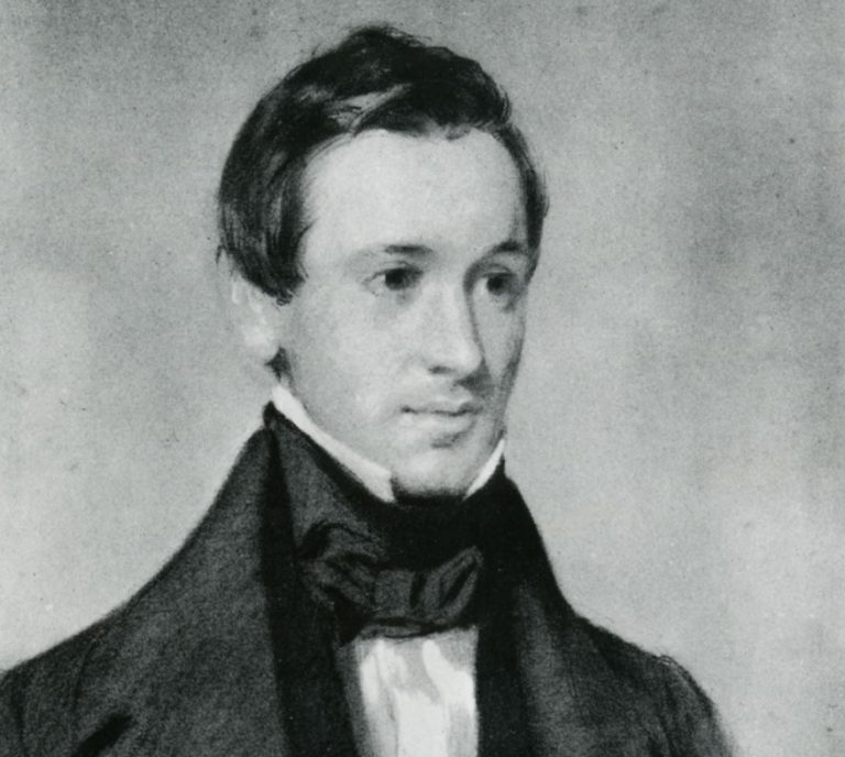 black and white photograph of a man from the shoulders up wearing a black cravat