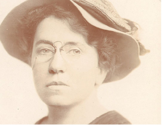 Sepia-toned photo of a woman wearing a hat and glasses