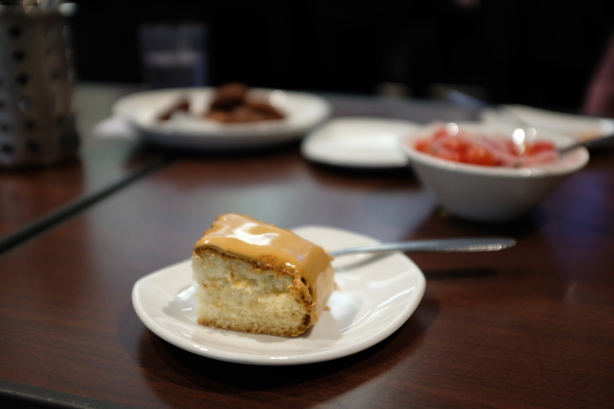Photo of a piece of cake on a plate, and two indistinct food items in the background