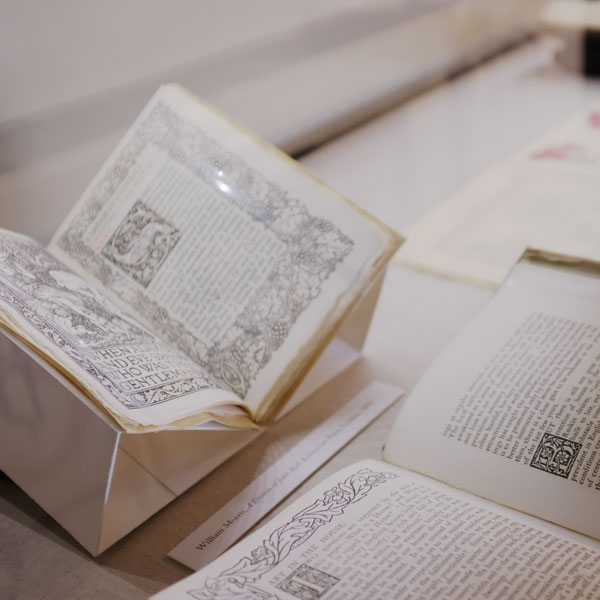 Partial views of open texts that are sitting on book rests. The border pages are heavily illustrated and dense with text.