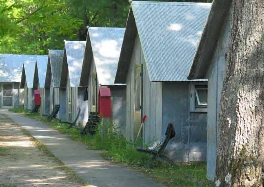 Photo of a row of 8 identical small buildings, with the trunk of a tree in the foreground and a paved path in front of them