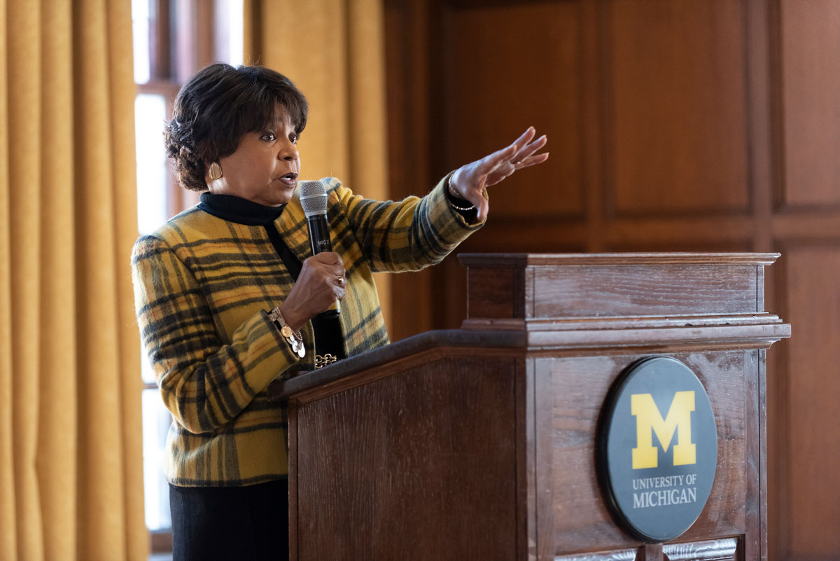 A woman standing at a podium, holding a microphone in one hand and gesturing with the other