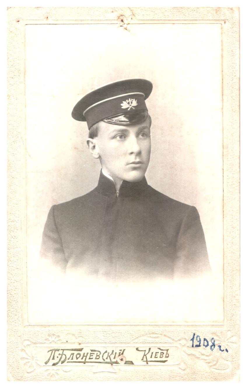 Black and white photo of a young man in uniform; handwritten text at the bottom includes a date, 1908, and text in Cyrillic